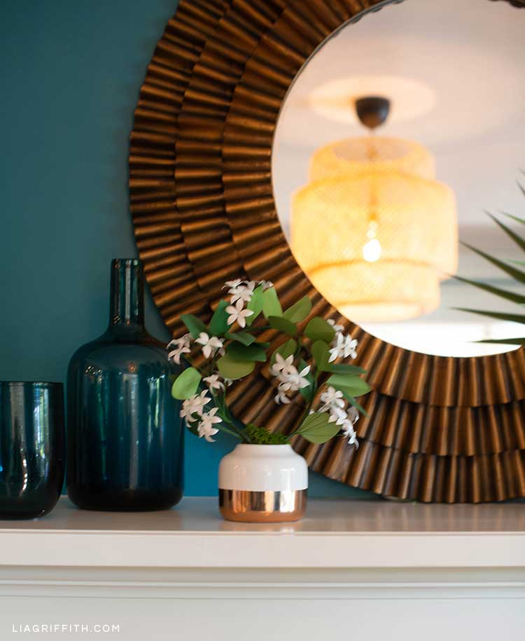 Fireplace mantel with round mirror, vase, and paper flowers
