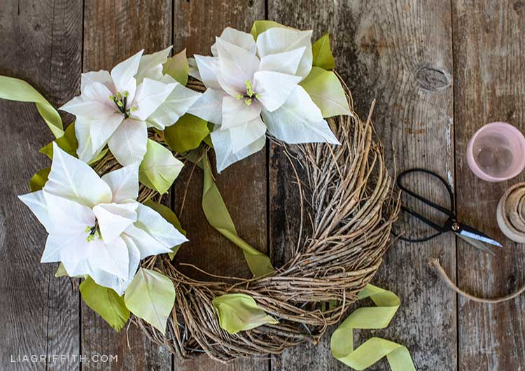 white crepe paper poinsettia wreath next to scissors and green ribbon