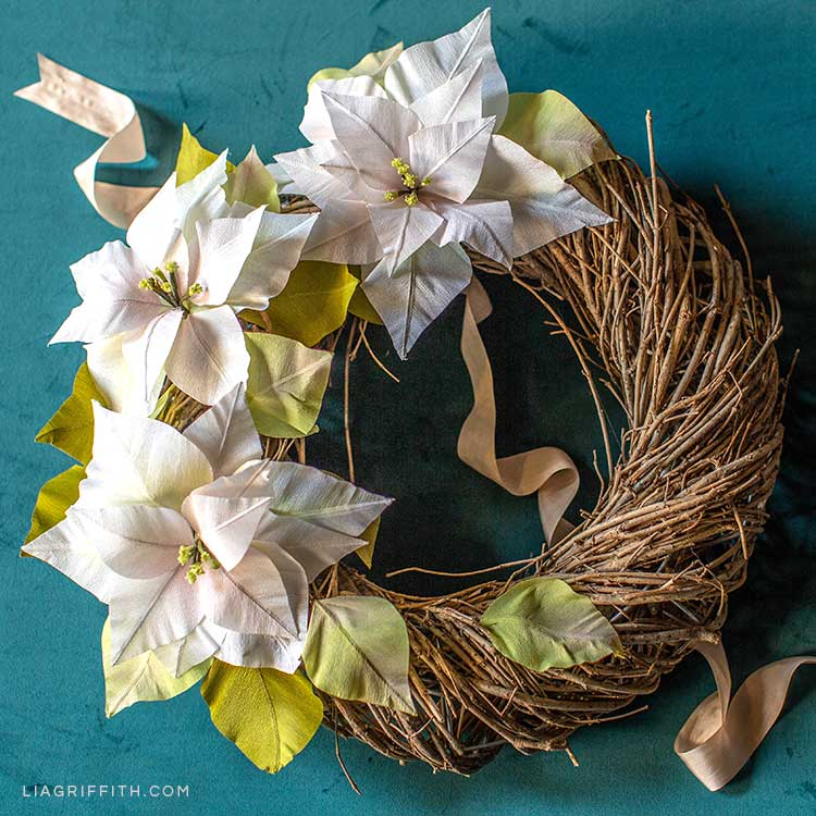 white crepe paper poinsettia wreath on teal background