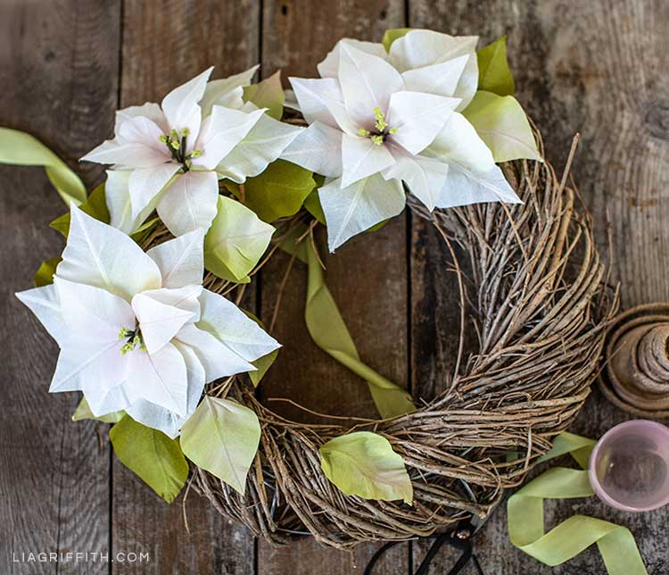 white crepe paper poinsettia wreath on wooden background with green ribbon running through it