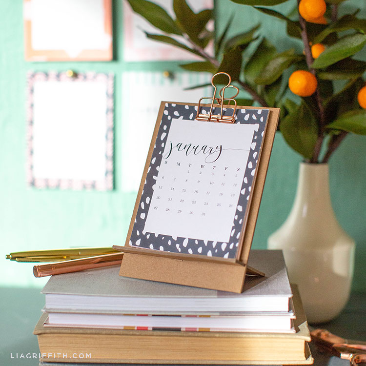 2019 desktop calendar on chipboard stand on top of books with paper kumquats in vase in background