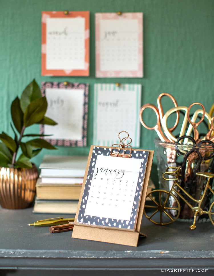 2019 desktop calendar resting on chipboard stand with monthly calendars hanging on wall in background with scissors, books, and potted plant