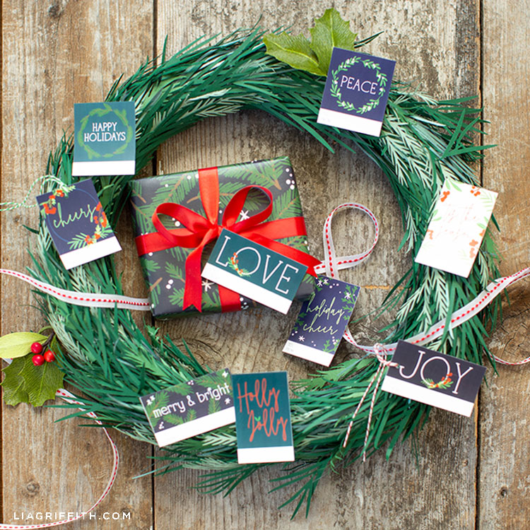paper winter greens wreath with paper holly leaves and holiday gift tags and wrapped gift