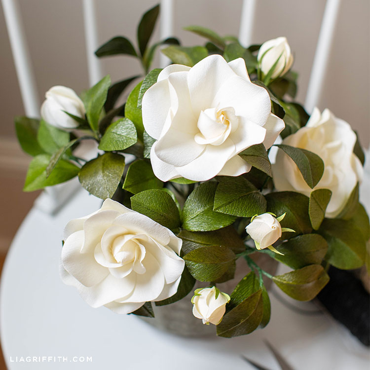 white crepe paper gardenia plant on white chair