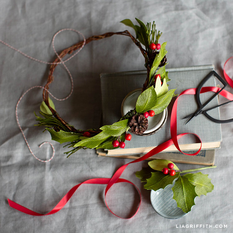 crepe paper evergreen head wreath with holly berries and pine cones on books with red ribbon and scissors