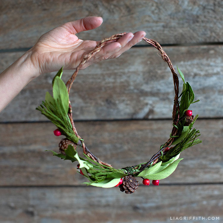 Hand holding crepe paper evergreen head wreath with holly berries and pine cones