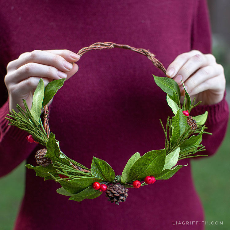 Woman holding crepe paper evergreen head wreath with holly berries and pine cones