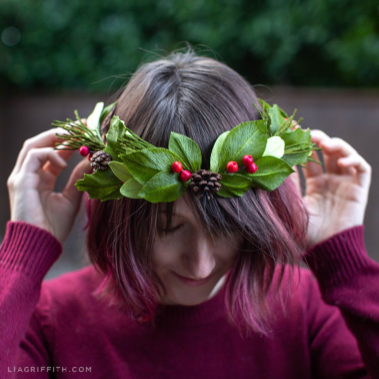 Woman putting crepe paper evergreen head wreath with holly berries and pine cones on her head