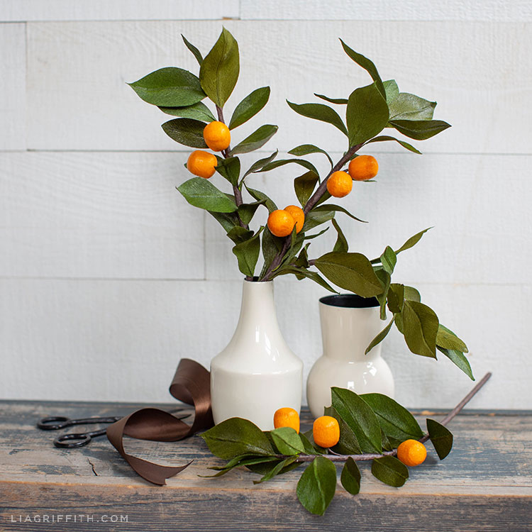 crepe paper kumquat branches in white vase