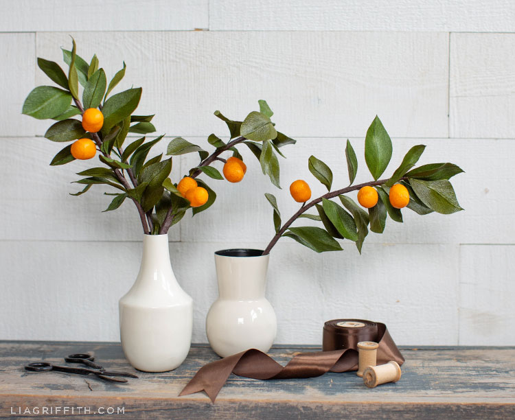 crepe paper kumquat branches in white vases on wood table with scissors and brown ribbon