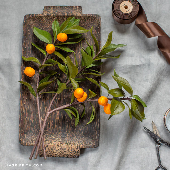 crepe paper kumquat branches on decorative wooden tray
