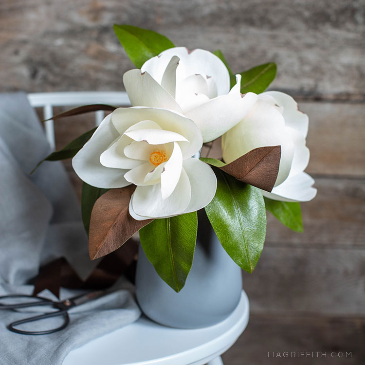 white crepe paper magnolia flowers in grey vase on grey stool