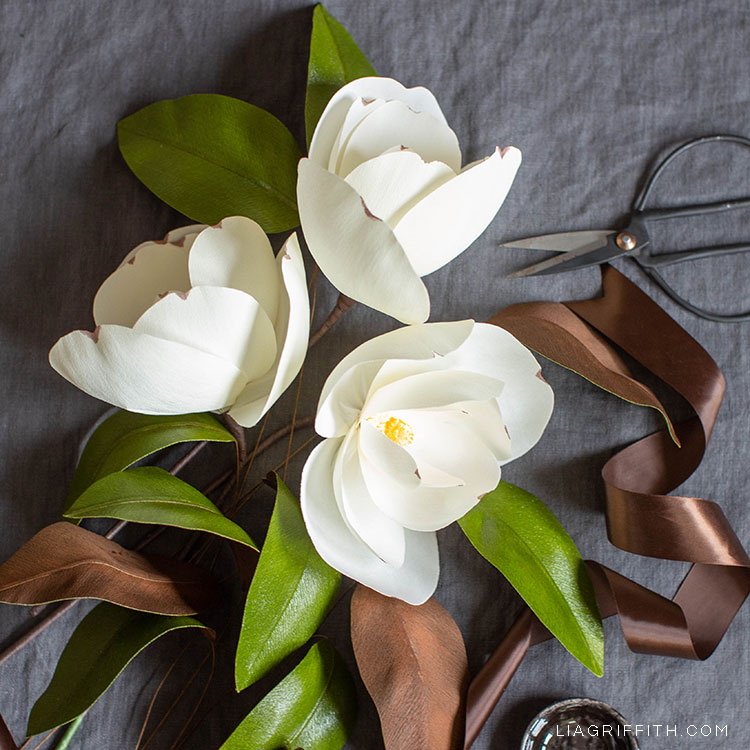 crepe paper magnolias on grey sheet next to brown ribbon and scissors