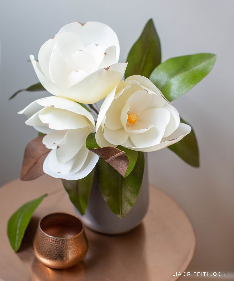 white crepe paper magnolias in grey vase on copper table