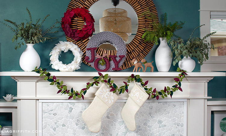 holiday mantel with felt greenery garland, felt monogrammed white stockings, felt joy, felt reindeer, red ombré felt wreath, white felt wreath, grey knit wreath, and white vases with fresh greenery