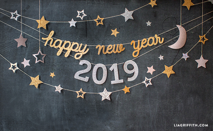 happy new year banner in glittery gold and 2019 in glittery silver with glittery gold and silver stars garland