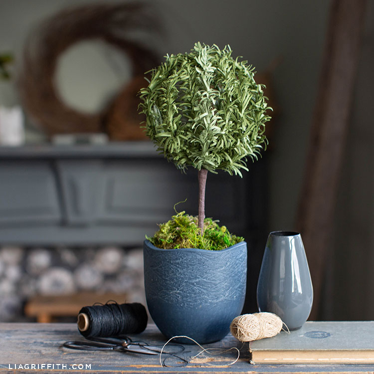 paper rosemary topiary on table with fireplace in background