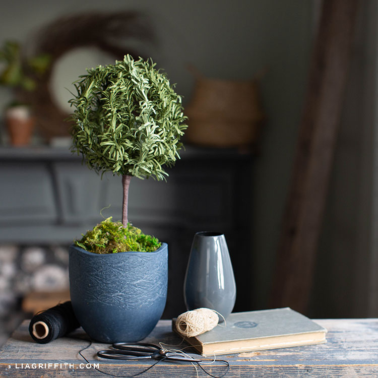 paper rosemary topiary next to small grey vase, thread, and book