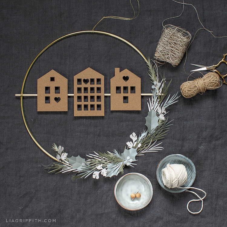 Scandi house and greenery wreath on grey sheet next to twine and scissors