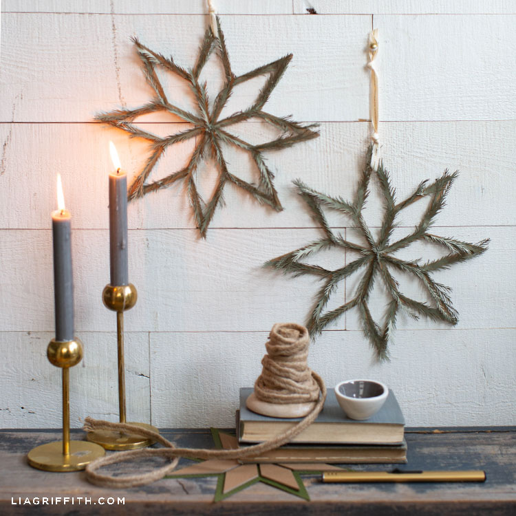 DIY Scandi star décor hanging on wall above shelf with candles and books