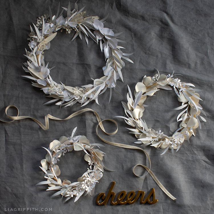 white paper eucalyptus wreath in three sizes on grey sheet with gold cheers sign and ribbon