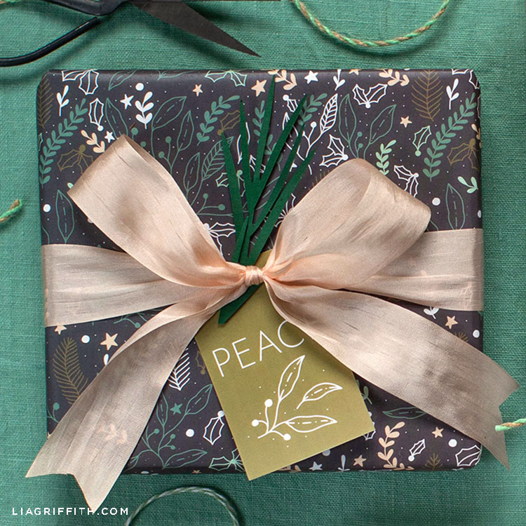 winter gift wrap featuring eucalyptus, fern leaves, holly leaves and berries, stars, and small snowballs on present with pink bow and peace gift tag