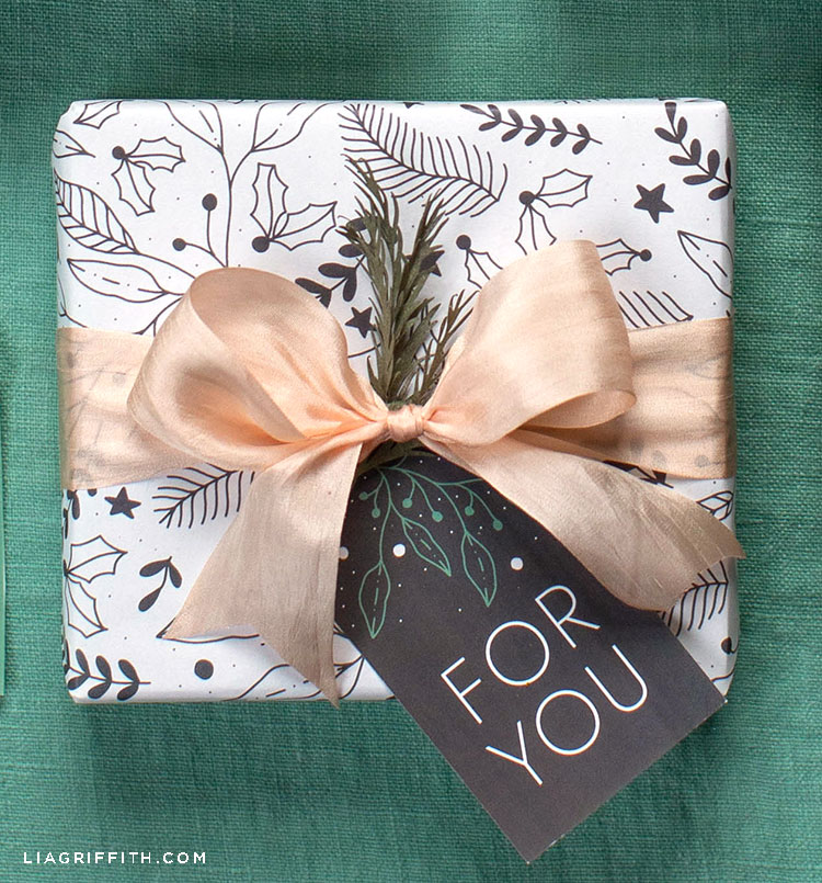 black and white winter gift wrap featuring holly leaves and berries on present with pink bow and for you gift tag