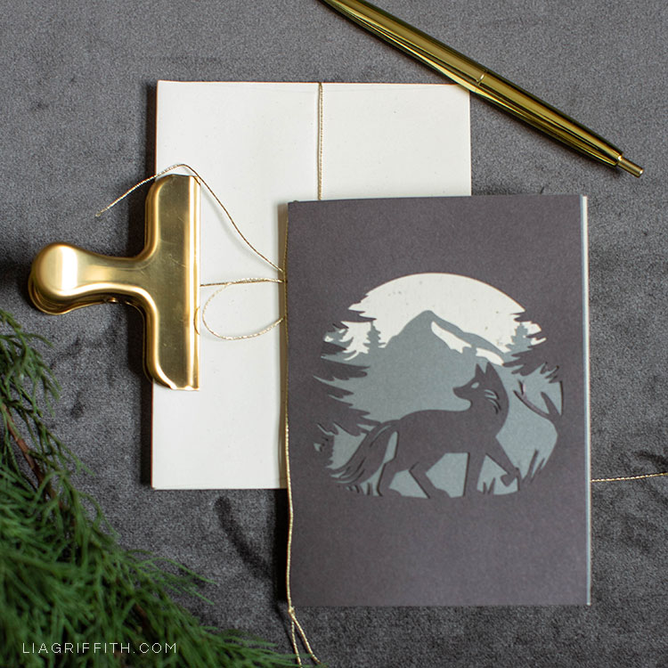 papercut woodland holiday card featuring wolf on stack of envelopes with gold clip and gold pen