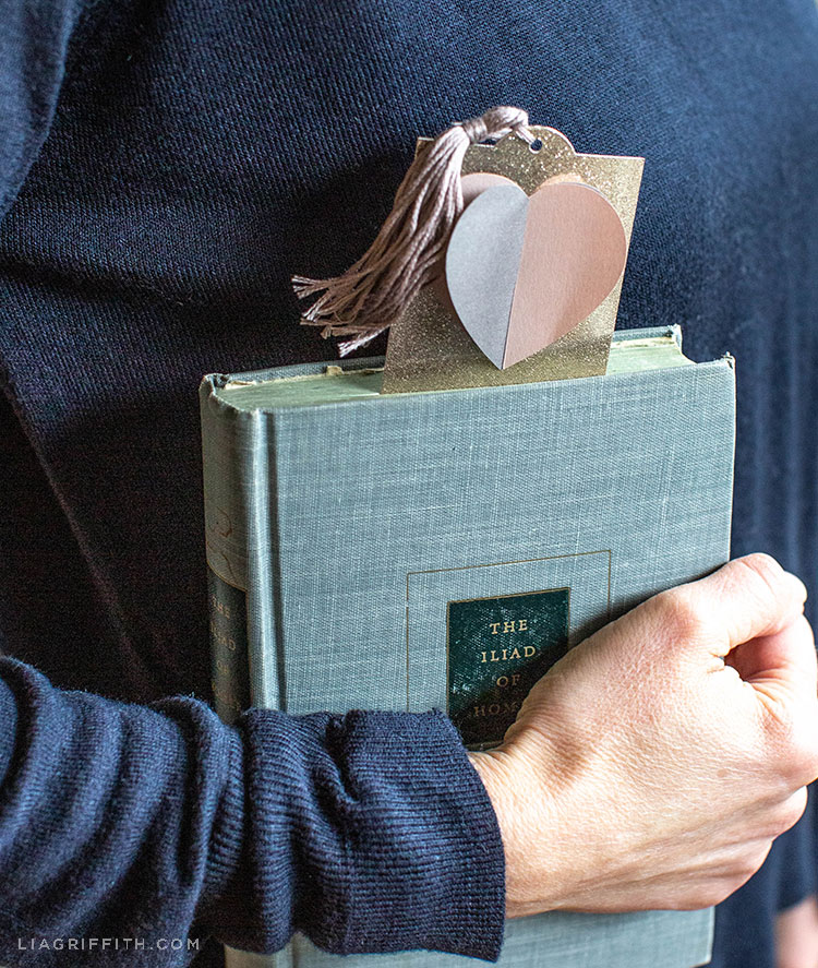 Person holding book with 3D paper heart bookmark inside