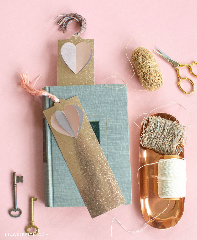 3D paper heart bookmarks with book, twine, scissors, and copper tray