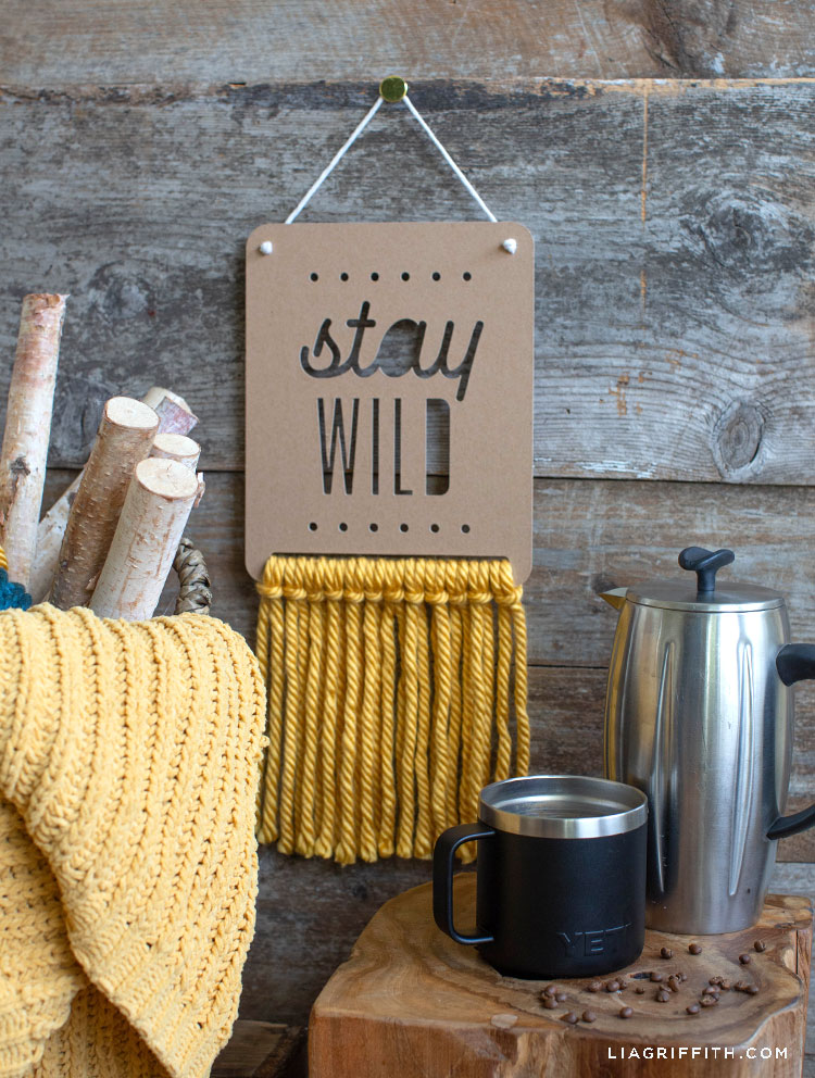 stay wild chipboard and yarn wall hanging next to coffee mug, blanket, and pieces of wood