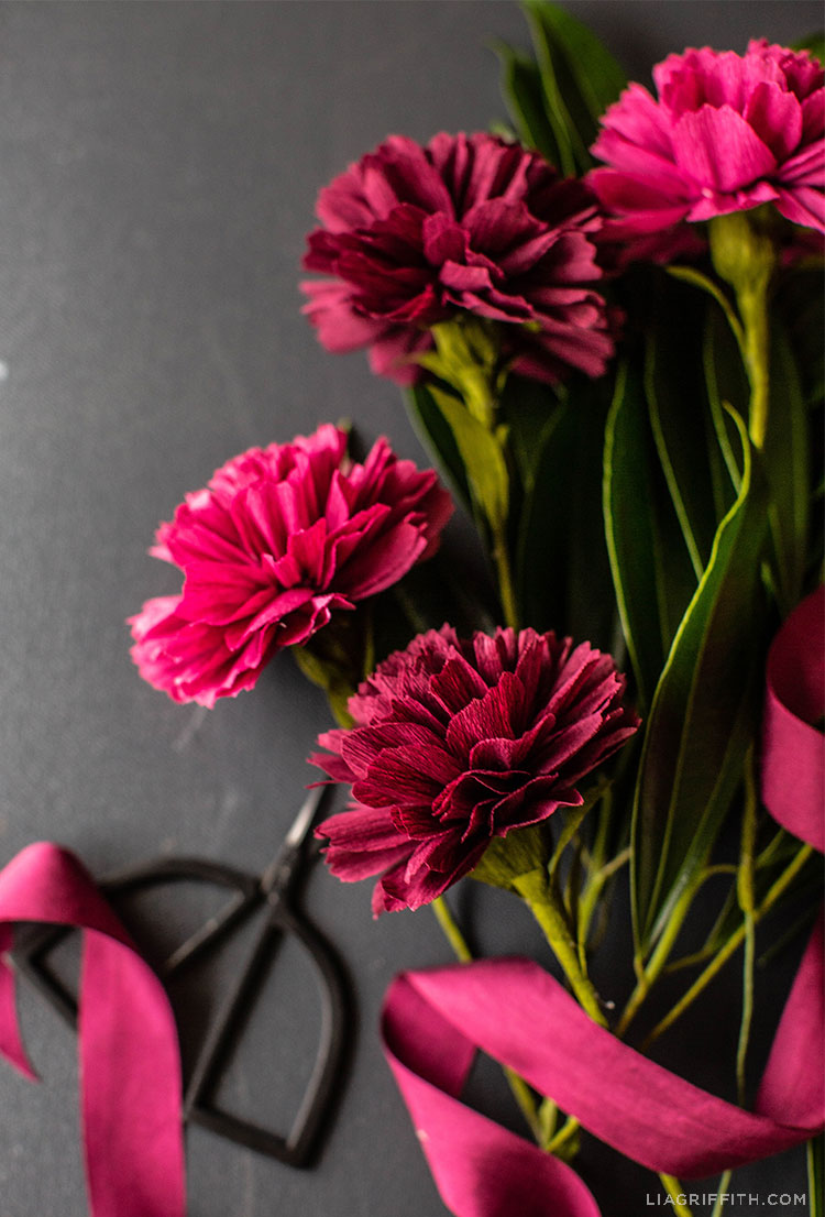 crepe paper carnations with pink ribbon and scissors