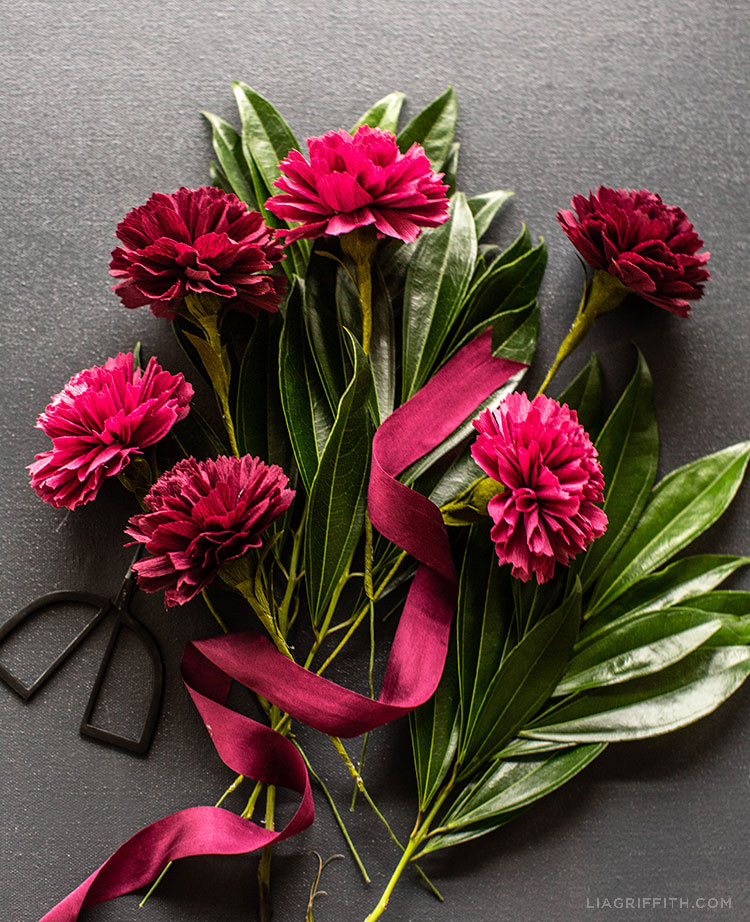 crepe paper carnations with leaves, red ribbon, and scissors