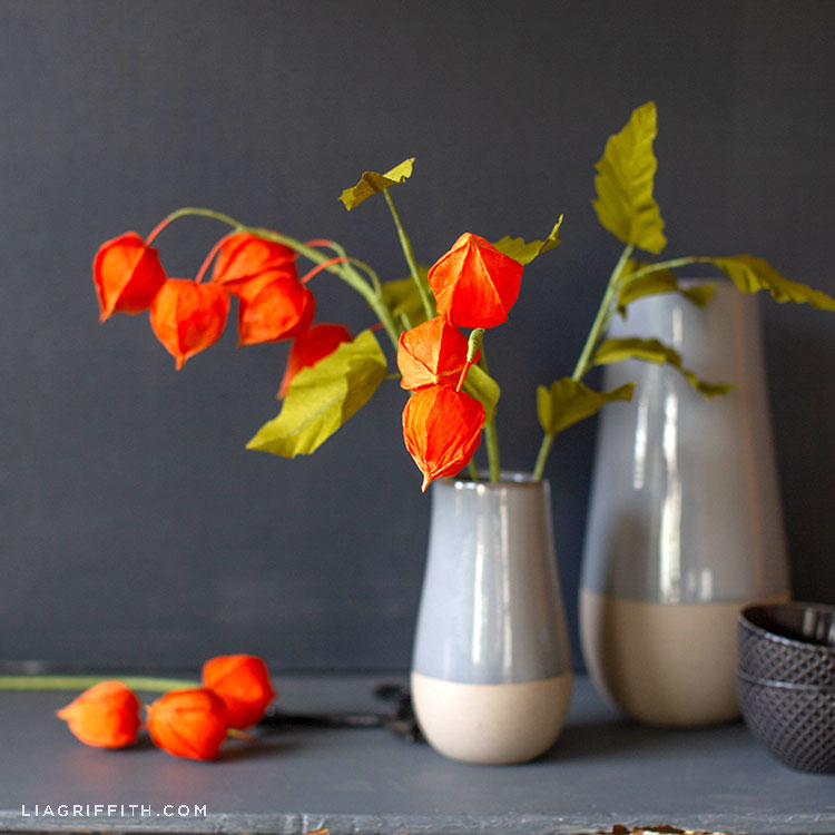 crepe paper Chinese lantern flowers in grey and cream vase on grey mantel