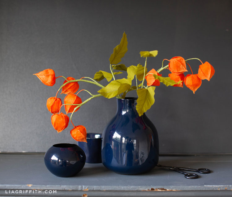 crepe paper Chinese lantern flowers in blue vase next to empty blue vases on grey mantel