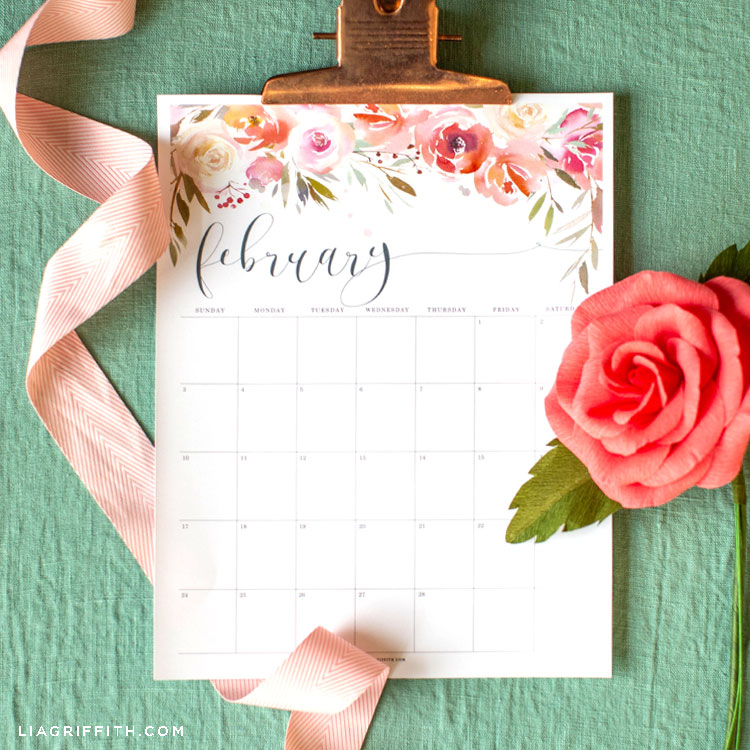 February 2019 printable calendar with pink paper camellia flower and pink ribbon against green background