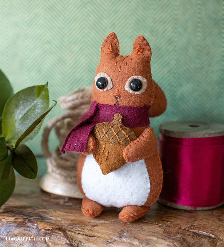 felt squirrel stuffie next to ribbon and plant