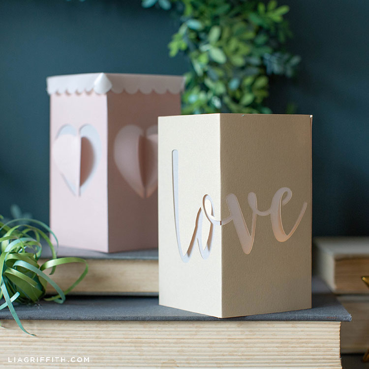 paper lanterns for Valentine's Day on books next to paper air plant