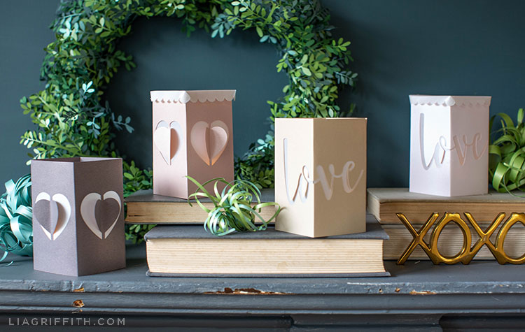 paper lanterns for Valentine's Day on top of books with paper plants, paper wreath, and XOXO sign on mantel