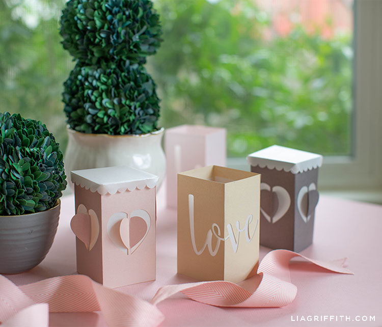 paper lanterns for Valentine's Day on pink table with paper boxwood in front of window