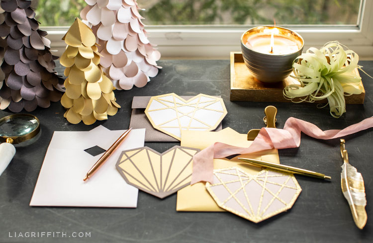 paper geometric heart cards on desk with paper heart trees, paper air plant, pens, and candle on gold tray