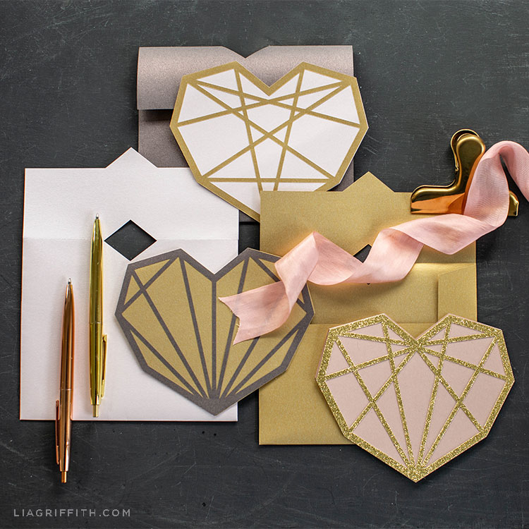 paper geometric heart cards with envelopes and pens on grey background