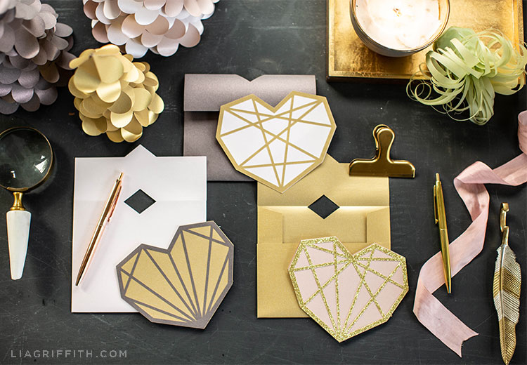 paper geometric heart cards with envelopes, paper heart trees, paper air plant, pens, magnifying glass, and clip