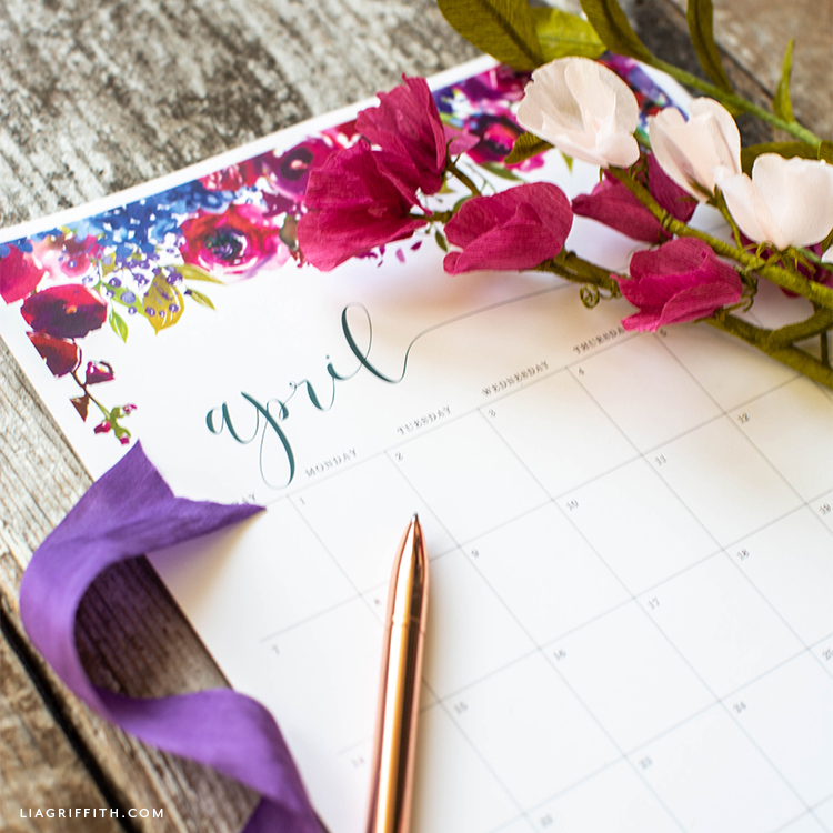 April 2019 printable calendar with purple ribbon, pen, and paper sweet pea blooms