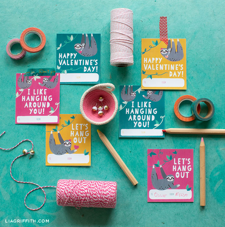 printable sloth valentines next to tape, pencils, and twine