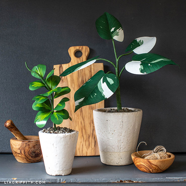 paper Hoya Kerrii plant in white pot next to paper plant on grey mantel with wooden board and wooden bowls
