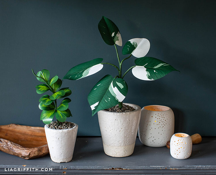 paper White Knight Philodendron in white pot next to paper Hoya plant in white pot on mantel next to candles and wood decor