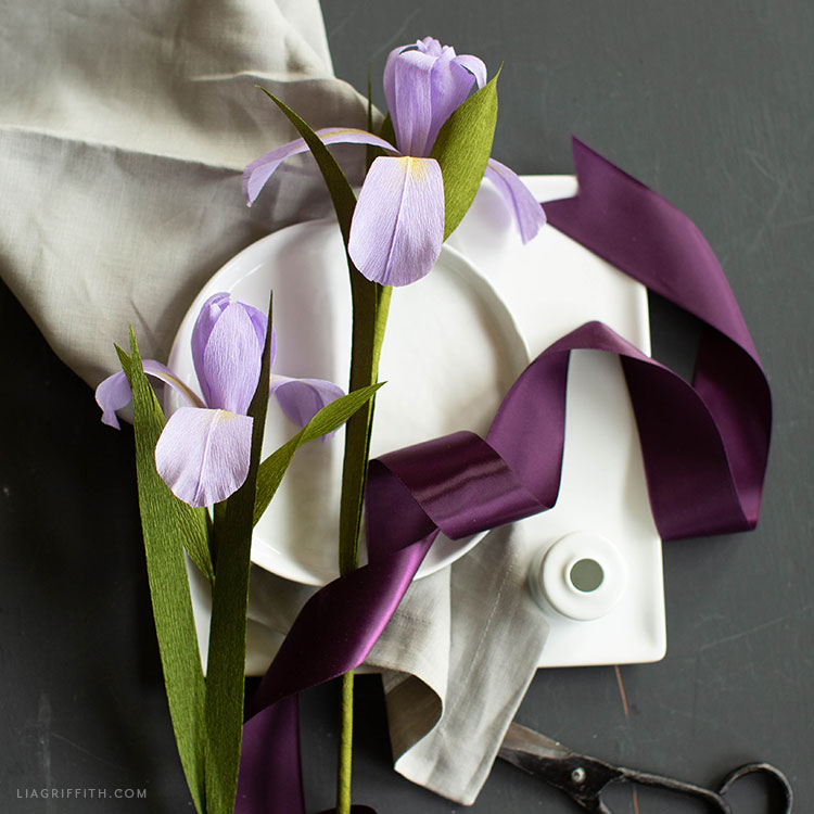 purple crepe paper dutch iris flowers with purple ribbon on white bowl and sheet