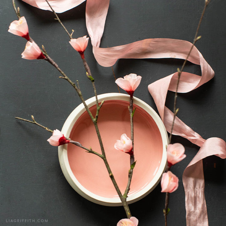 crepe paper flowering quince branches on white and pink bowl with pink ribbon