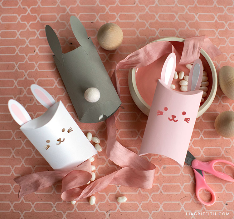 papercut bunny pillow boxes with pink ribbon, scissors, wooden eggs, and bowl with candy
